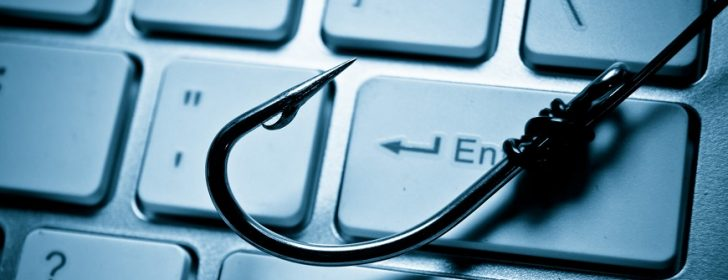 a fish hook on computer keyboard representing phishing attack on computer system